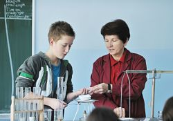 teenager doing science experiment with teacher