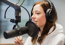 woman with headphones in front of microphone