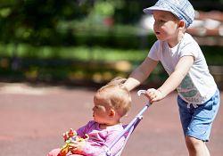 boy pushing baby in stroller