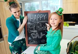 girl and mother making Happy St. Patrick's Day sign