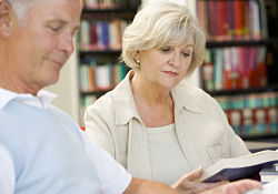 Adults discussing book in library