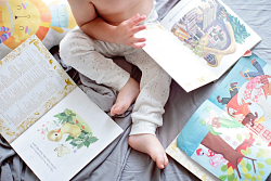 Baby sitting on blanket surrounded by books