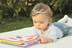 Baby on a blanket with a book