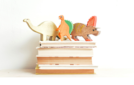 stack of children's books with toy dinosaurs